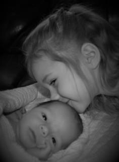 Big sister kissing newborn sibling in black and white